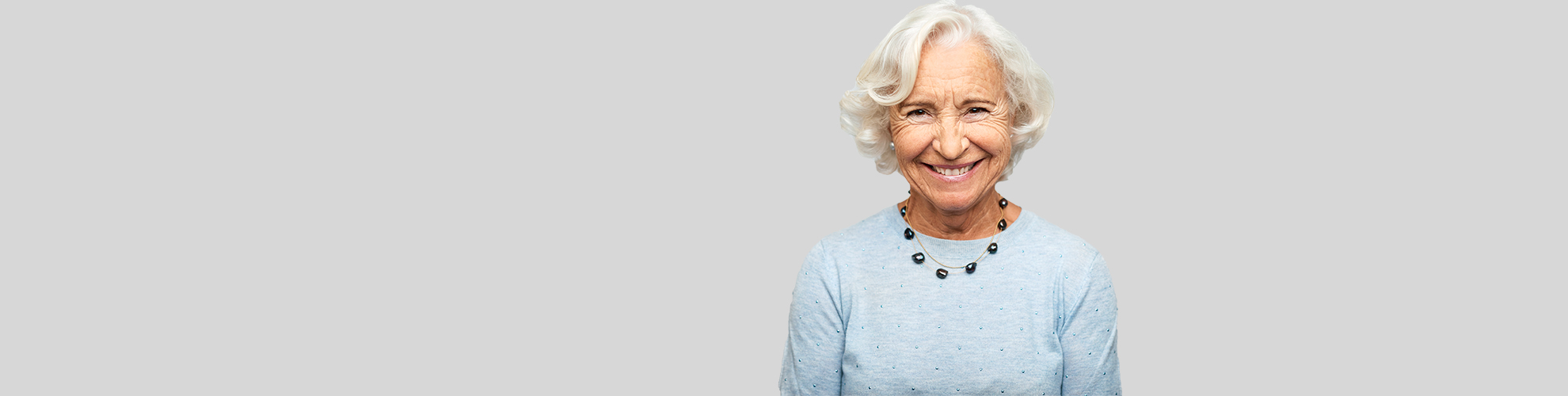 Elderly woman smiling from lowered risk of heart disease